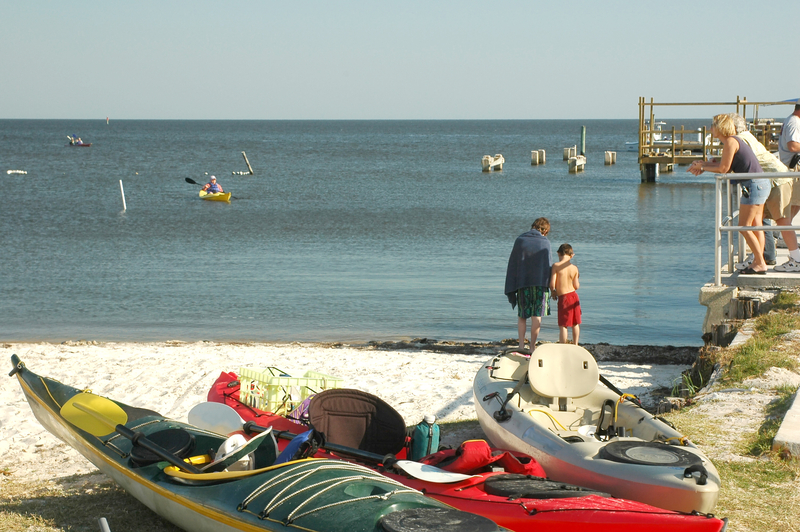 Kayaks await paddlers on the beach at Cedar Key, Florida on the Gulf of Mexico.