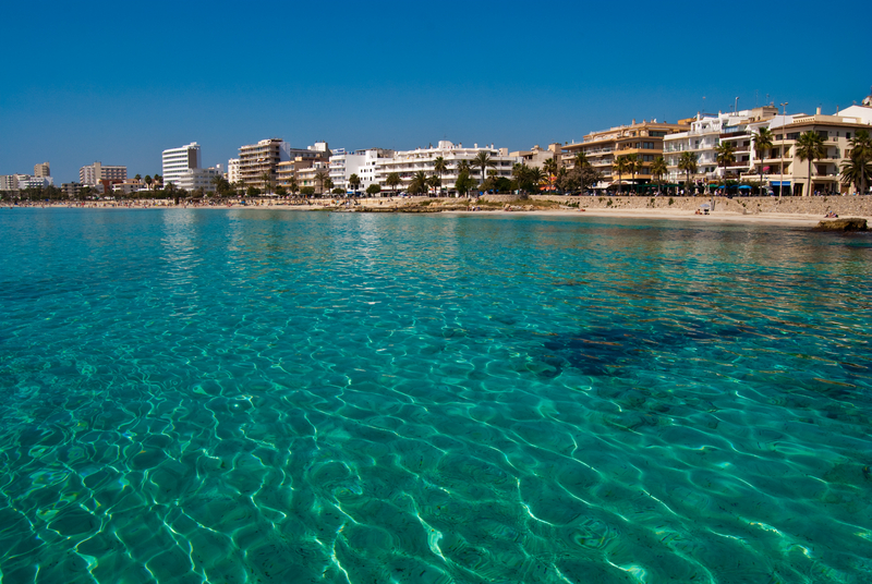 Turquoise water of Mediterranean Sea and Cala Millor resort town center, Majorca island, Spain